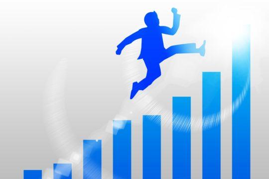 棒グラフとジャンプする人の画像